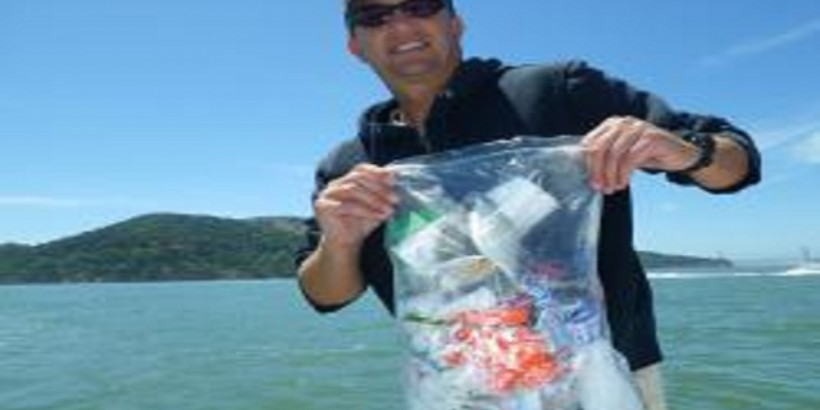 Dozens of plastic pollution items were found and recovered from San Francisco Bay on June 16, World Sea Turtle Day. This plastic bag, one of the litter items recovered, quickly filled with styrofoam pieces, plastic cups, and the remnants of a baseball cap. Nick Drobac, Executive Director of The Clean Oceans Project, holds the recovered items. Photo: Chris Pincetich